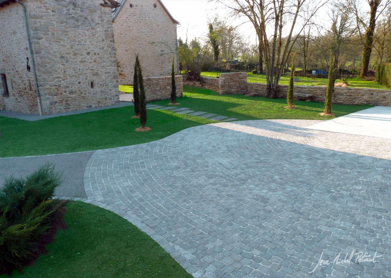 Composition avec pavés aux abords d'une maison en pierre